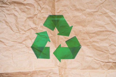 Green recycle arrow on craft paper