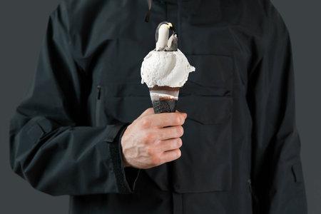 Man in black raincoat holding melting ice cream cone with penguins.