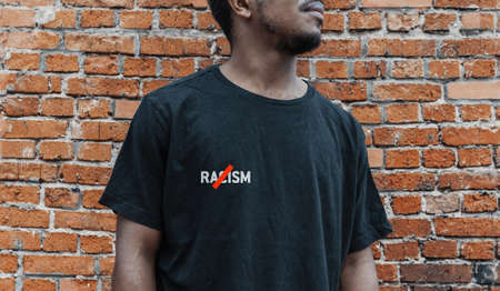 A man in black T shirt with no racism inscription against red brick wall
