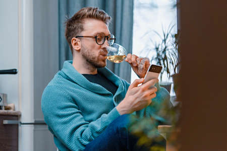 Man talking to his friends by video call while drinking wine.