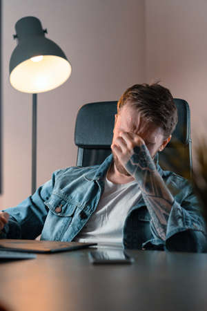 Tensed man sitting at home office after work.
