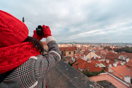 Young woman with big red scarf taking photos of old town