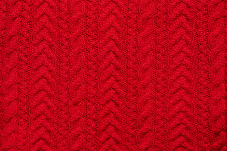 Red knitted textured sweater pattern.