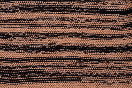Knitted fabric of beige, brown and black colors.