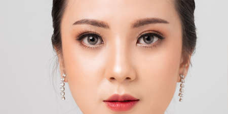 Asian female Eye with Extreme Long False Eyelashes. Eyelash Extensions. Makeup, Cosmetics, Close up macro eye woman. Cosmetic contact lenses. Closeup face asian woman perfect skin. Фото со стока