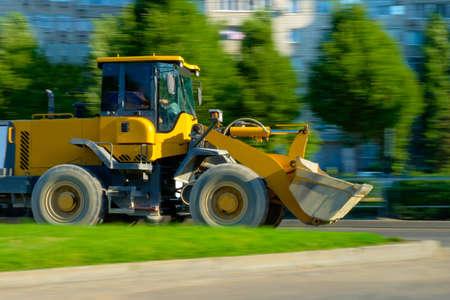 cargador frontal: amarillo cargador frontal se mueve en el camino Foto de archivo