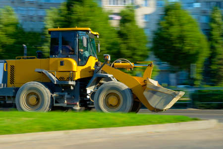 front loader: yellow front loader moves on the road Stock Photo