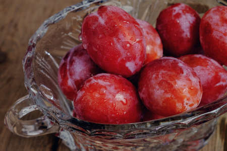crystal bowl: bright fresh plums in a crystal bowl on the old wooden boards