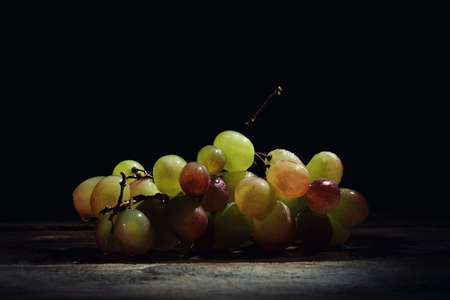 Beautiful fresh wet grapes on a wooden table on a black background. Фото со стока