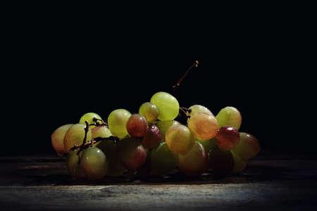 hojas vid: Uvas mojadas frescas hermosas en una mesa de madera sobre un fondo negro. Foto de archivo