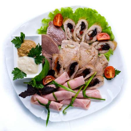 charcutería: embutidos de carne sabrosa vaus servido en un plato blanco y decorado con vegetación.