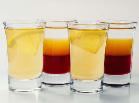 shot glasses: small glass shot glasses with alcohol on a white background.