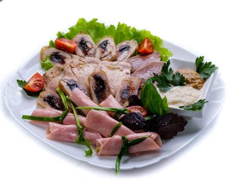 charcuter�a: embutidos de varios sabrosa carne servido en un plato blanco y decorado con vegetaci�n.