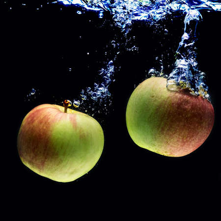 green apples: delicious two-color apple in water on a black background.