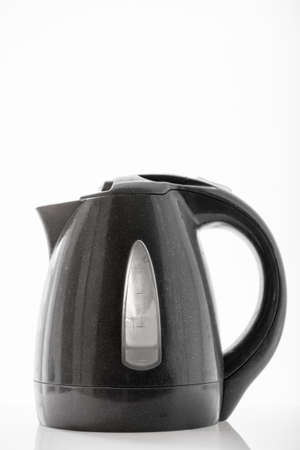 colored window: Electric kettle on a dark colored window with light from the window.