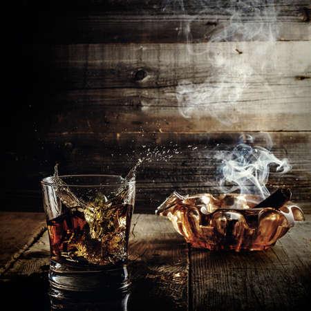 cigarro: el whisky y el cigarro en la mesa iluminaban el arte de la luz mística. Foto de archivo