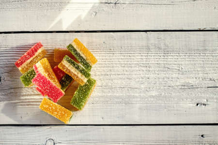burlap sac: Colorful delicious marmalade on wooden boards, illuminated by the light from the window. Stock Photo