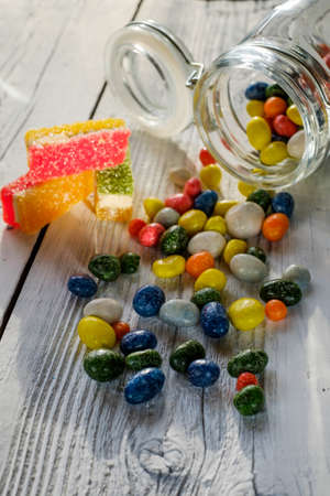 spilling: Yellow striped candy bag spilling its candies over a white wooden table Stock Photo