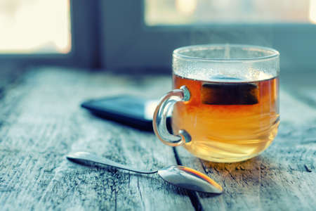 hot day: Hot tea cup on a frosty winter day window background Stock Photo