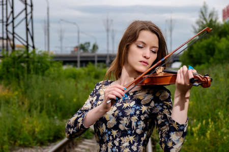 symphonic: Beautiful woman performer with violin in nature Stock Photo