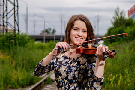 Beautiful woman performer with violin in nature Stock Photo
