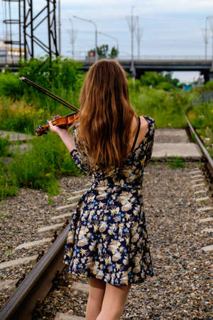 virtuoso: Beautiful woman performer with violin in nature Stock Photo