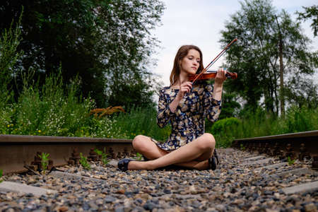 performer: Beautiful woman performer with violin in nature Stock Photo