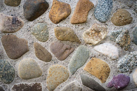 The stones embedded in the concrete foundation and background Stock Photo