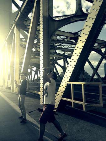 personnes qui marchent: Les gens � pied et en prenant en photo promenade � travers un pont C'est un moment de joie Banque d'images