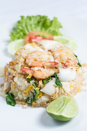close up fried rice with seafood and lime on white dish photo