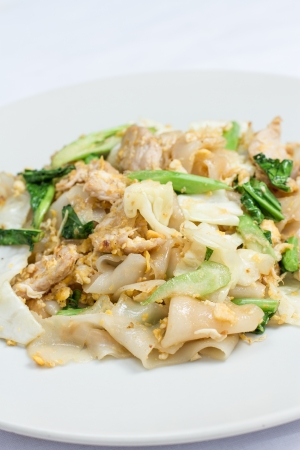 stir fired thin noodles with soy sauce and pork and Kale on white dish photo