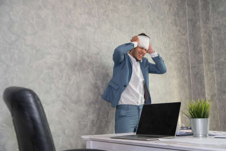 Sick business man touching his head with hands while working hard at office