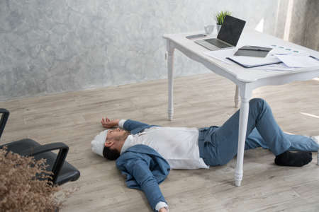 Sick businessman sleeping on floor while using laptop to work hard at office Stock Photo