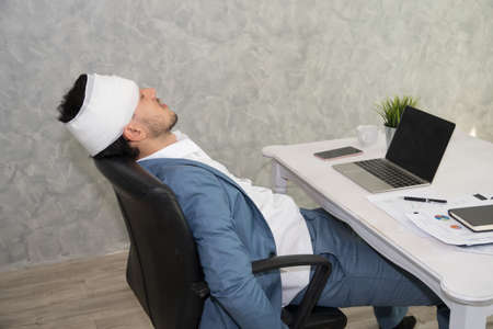 Sick business man wearing bandages his head using laptop to work hard at office
