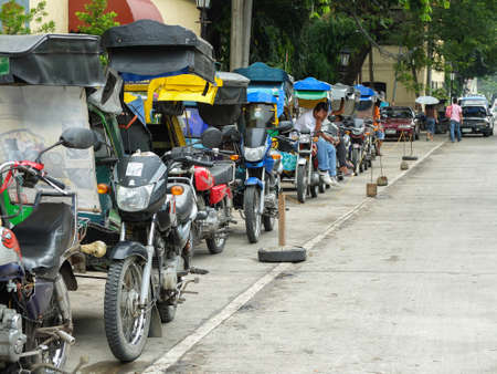 means of transportation: VIGAN, PHILIPPINES - JULY 25, 2015 : Tricycles in  Historic Town of Vigan. Tricycles are an indigenous form of the auto rickshaw and are a common means of public transportation in the Philippines Editorial