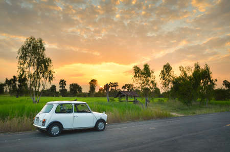cooper: THAILAND - OCT 7, 2014 : Classic Mini Cooper and sunset over Tungkula rice fields Editorial