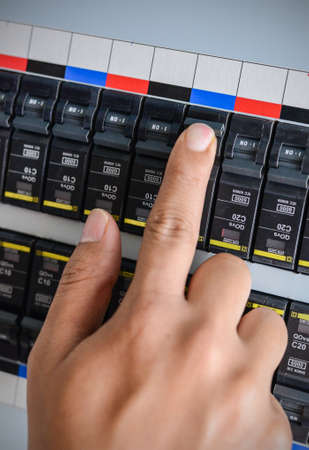Hand with finger on circuit breaker switch, about to turn on the system