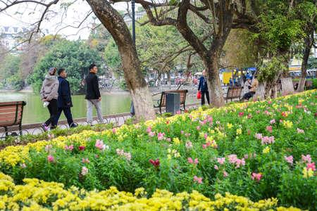 Hanoi, Vietnam - Feb 20, 2017 :  Peopla walking by Flower Garden at Hoan Kiem Lake, the center of Ha Noi, Vietnam, in the evening Editorial