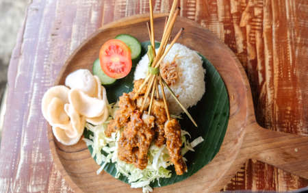 Chicken Sate rice ( Nasi sate) served eggs, prawn crackers and chicken satay and peanut sauce, Indonesian cuisine