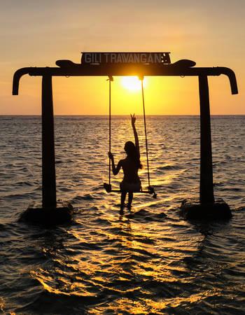 Gili Trawangan, Indonesia - September 11, 2017:  Silhouette of Beautifull Gate with girls swing above ocean sunset.   Gili Trawangan island, Lombok, Indonesia