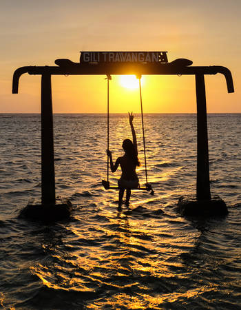 Gili Trawangan, Indonesia - September 11, 2017:  Silhouette of Beautifull Gate with girls swing above ocean sunset.   Gili Trawangan island, Lombok, Indonesia
