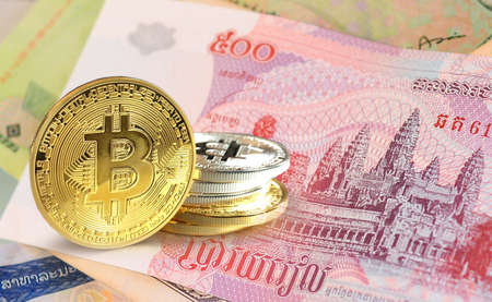 Bitcoin coins on Cambodian riel banknote, Cryptocurrency concept photo Stock Photo