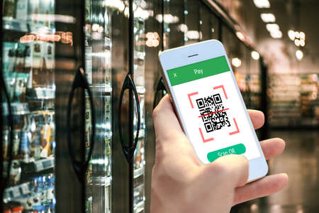 Hand holding smartphone to scan QR code payment , online shopping , cashless technology concept.