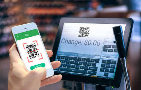 Hand holding smartphone to scan QR code payment , online shopping , cashless technology concept. Zdjęcie Seryjne