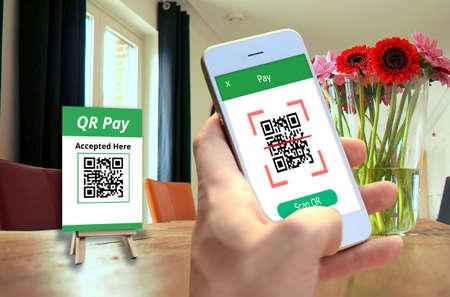 Hand met smartphone om QR-codebetaling, online winkelen, geldloos technologieconcept te scannen. Stockfoto