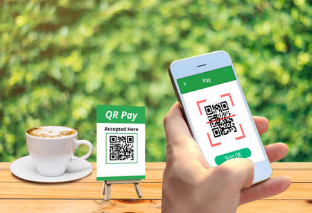 Hand holding smartphone to scan QR code payment , online shopping , cashless technology concept. Фото со стока