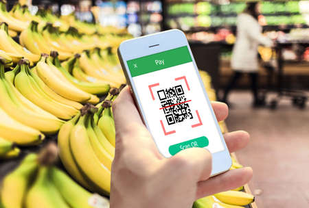 Hand holding smartphone to scan QR code payment , online shopping , cashless technology concept. Stock Photo