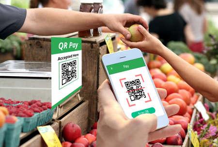 Hand met smartphone om QR-codebetaling, online winkelen, geldloos technologieconcept te scannen.