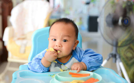 Asian baby boy 6 months old eating with Baby Led Weaning (BLW) method, Baby eat by himself, Self-Feeding