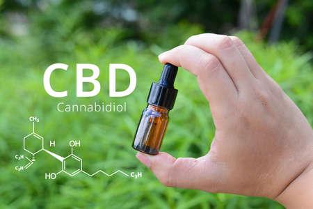 Cannabidiol (CBD) molecule formula with Hand holding CBD Oil glass bottle